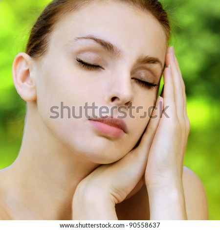 Portrait of naked dark-haired woman propping up her face with eyes closed at summer green park. - stock photo