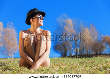 portrait of naked girl with hat and sunglasses, outdoors - stock photo