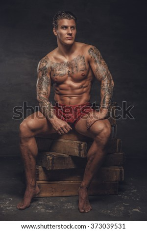 Portrait of naked muscular guy with tattooes on his body.