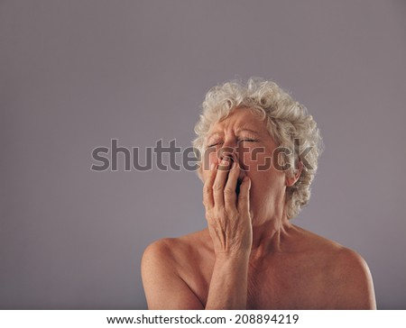 Portrait of naked senior woman yawning. Tired looking old female with copy space on grey background. - stock photo