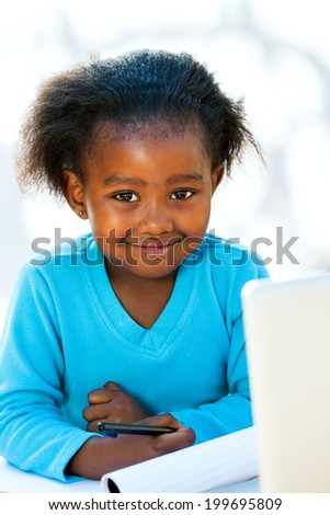 Portrait of native African kid at desk with notebook and laptop. - stock photo