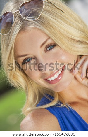 Portrait of naturally beautiful woman in her twenties with blond hair and blue eyes & heart shaped sunglasses - stock photo