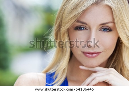 Portrait of naturally beautiful woman in her twenties with blond hair and blue eyes, shot outside in natural sunlight - stock photo
