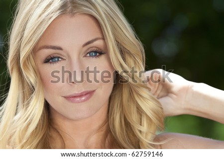 Portrait of naturally beautiful woman in her twenties with blond hair and blue eyes, shot outside in sunlight with a natural green background