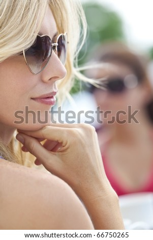 Portrait of naturally beautiful woman in her twenties with blond hair wearing heart shaped sunglasses, shot outside in natural sunlight - stock photo