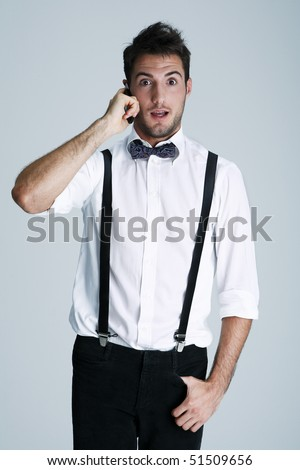 Portrait of nerdy young man in suspenders on the phone, studio shot - stock photo