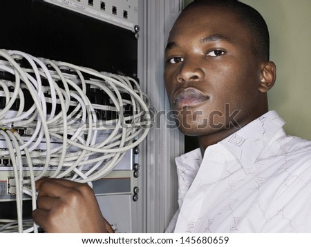 Portrait of network engineer working in server room - stock photo
