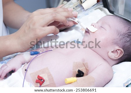 Portrait of newborn baby and hand inside incubator - stock photo