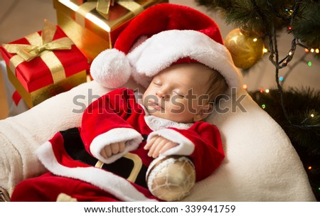 Portrait of newborn baby boy in Santa clothes lying under Christmas tree - stock photo