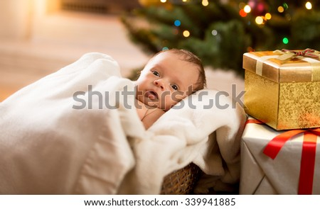 Portrait of newborn baby boy lying under blanket next to Christmas tree and gift boxes - stock photo