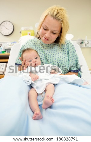 Portrait of newborn baby girl in mothers lap in hospital room - stock photo