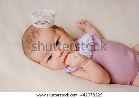 Portrait of newborn baby girl with opened eyes in a violet suit with white ruffles and a crown on her head is touching her lips