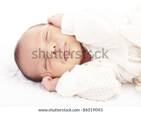 portrait of newborn baby sleeping in a bed ober white background