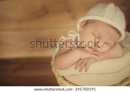Portrait of Newborn Baby Sleeping in Subtile Hat on Soft Blanket - stock photo