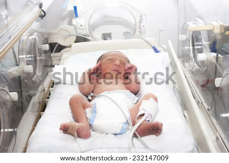 Portrait of newborn baby sleeping inside incubator - stock photo