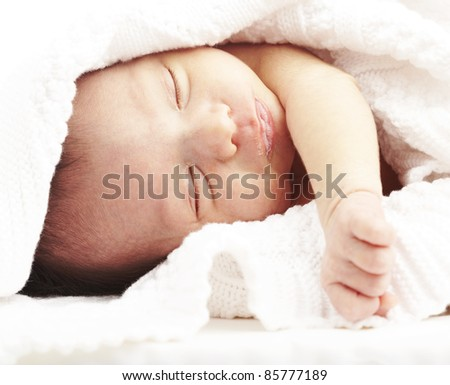 portrait of newborn baby sleeping on a bed under a towel - stock photo