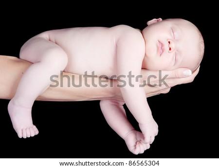 Portrait of newborn baby sleeping on mothers hand on black background - stock photo