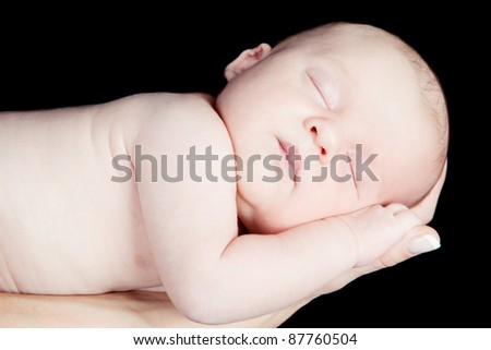 Portrait of newborn baby sleeping on mothers hand on black background - stock photo