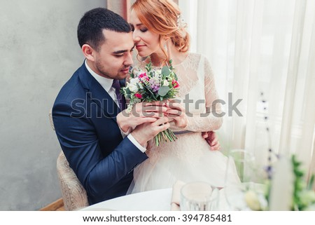 Portrait of newly wed couple with flower bouquet indoors - stock photo