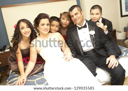 Portrait of newly wedded couple with bridesmaids and groomsmen sitting on bed. Horizontal shot. - stock photo
