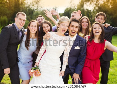 Portrait of newlywed couple having fun with bridesmaids and groomsmen in green sunny park - stock photo