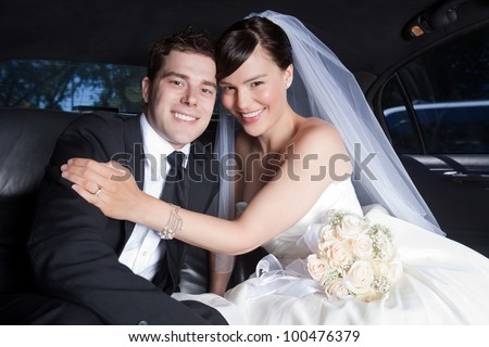 Portrait Of Newlywed Couple Smiling Sitting In Limousine. - stock photo