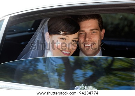 Portrait Of Newlywed Couple Smiling Sitting In Limousine - stock photo