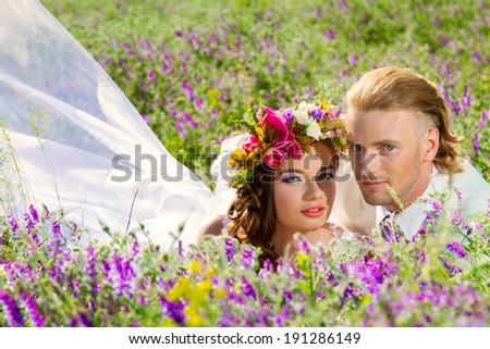 portrait of newlyweds in love in a summer blossoming field - stock photo