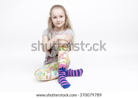 Portrait Of Nice and Cute Caucasian Blond Kid Posing Against White Background. Sitting With Hands Crossed. Positive Facial Expression.Horizontal Image - stock photo