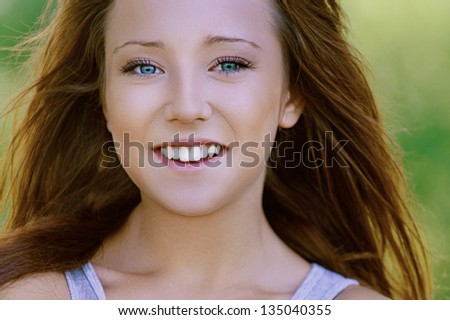 Portrait of nice smiling young woman, against background of summer green park. - stock photo