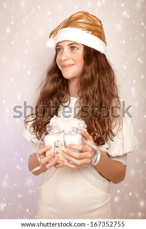 Portrait of nice teen girl holding in hands festive gift box and looking on the side, little Santa Claus helper, Christmas time magic concept - stock photo