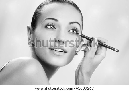 Portrait of nice young  gorgeous woman  getting busy with her makeup