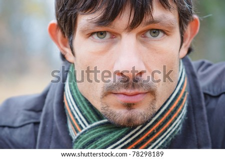 Portrait of nice young man on background of nature sunny day - stock photo