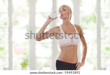 Portrait of nice young woman drinking water on shore - stock photo