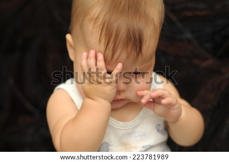 Portrait of nine month baby rubbing his eyes - stock photo