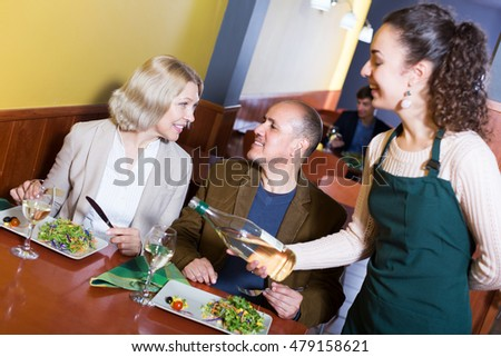 Portrait of nippy and ordinary smiling elderly couple having dinner