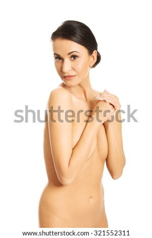 Portrait of nude woman covering her breast and looking at the camera.