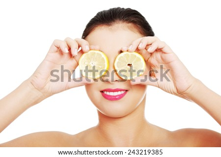 Portrait of nude woman with lemon on eyes. - stock photo