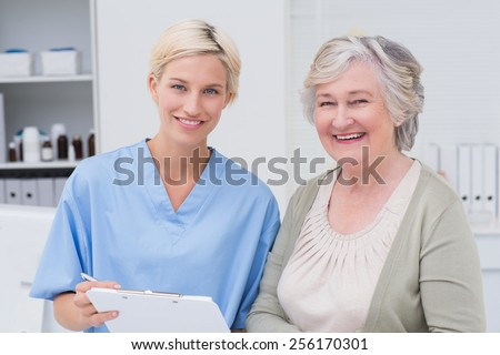Portrait of nurse and patient smiling in clinic - stock photo