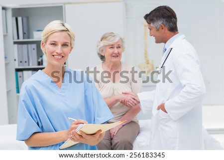 Portrait of nurse making reports while doctor and patient shaking hands in background at clinic - stock photo