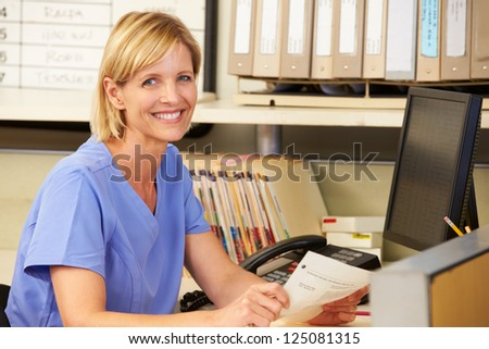 Portrait Of Nurse Working At Nurses Station - stock photo