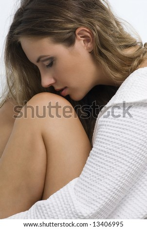 portrait of of a young woman with white bathrobe kissing her knee