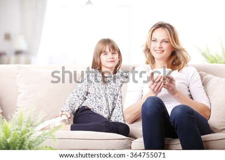 Portrait of of smiling mother and adorable daughter sitting on couch.