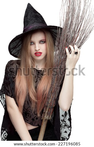 Portrait of of young woman in black witch costume with a broom isolated on white background. Halloween - stock photo
