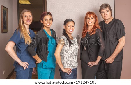 Portrait of office staff standing in office area. - stock photo