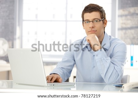 Portrait of office worker man sitting at office desk using laptop computer, looking at camera.?