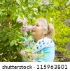 Portrait of old lady, European, with lilac shrub in garden. - stock photo