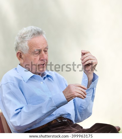 Portrait of old man sitting in courtyard - stock photo