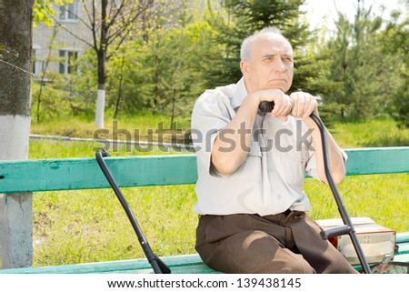 Portrait of old man sitting on the bench park waiting for someone - stock photo
