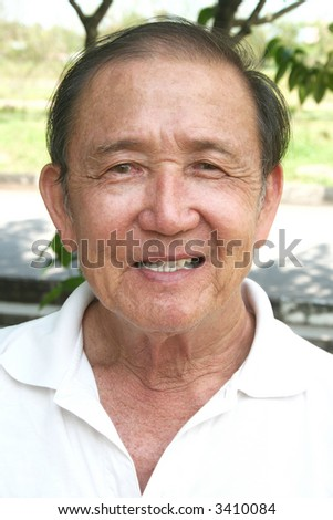 Portrait of old man smiling in the park - stock photo